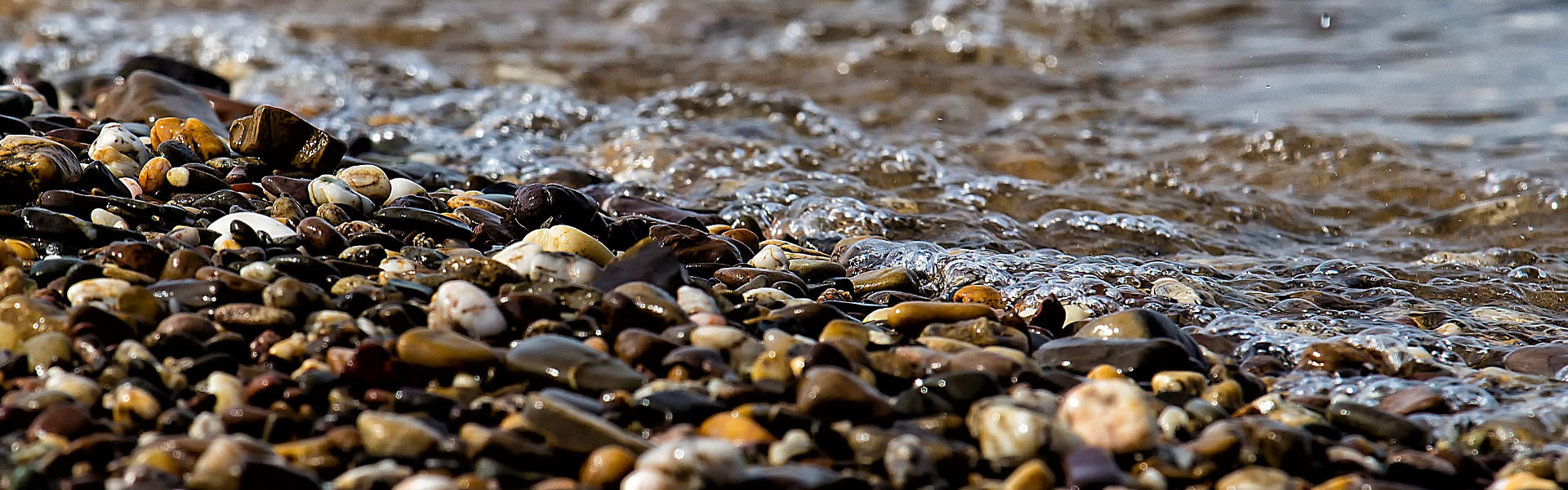 Stones near a beach with water lapping on the shore